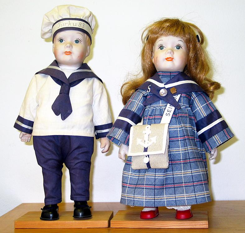Meriteemaan puetut poika- ja tyttönukke. Pojan lakissa teksti Turku 83 ja tytön laukun hihnassa Teksti Seinäjoki.