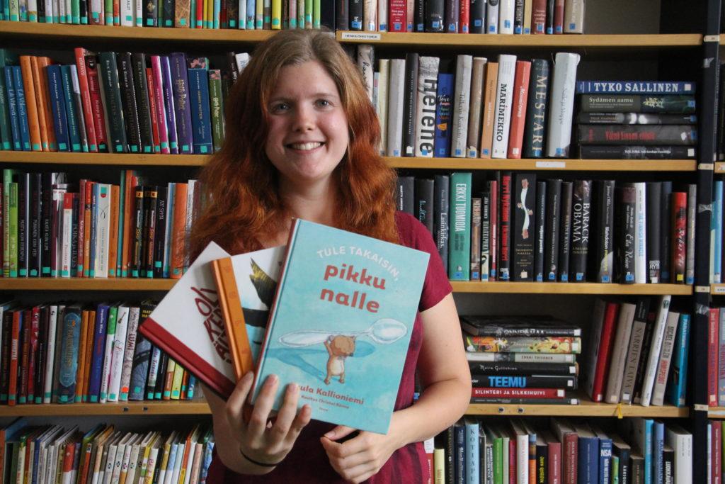 Nuori hymyilevä punatukkainen nainen seisoo kirjahyllyn edessä ja pitää käsissään kolmea kirjaa, joista päällimmäinen on nimeltään Tule takaisin pikku nalle.