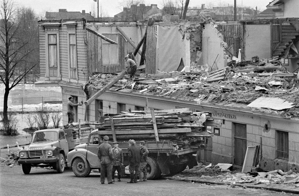 Puurakenteista merimieskirkkoa puretaan. Etualla kaksi aikakautensa kuorma-autoa, joihin purkujätettä lastataan usean miehen voimin.