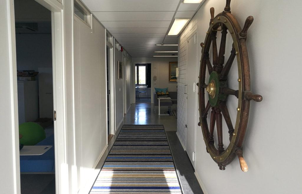 Herttoniemessä sijaitsevan Merimieskirkon keskustoimiston käytävä, jossa etualla oikealla seinälle ripustettu iso puinen ruori.
