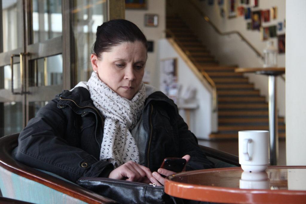Sisätiloissa nojatuolissa istuva, huivin kaulalleen kietaissut nainen katsoo älypuhelintaan. Edessä olevalla pöydällä on kahvimuki.