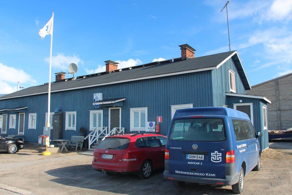 Sininen merimieskirkkorakennus, jonka edessä lipputangossa liehuva Merimieskirkon lippu sekä kaksi pysäköityä autoa, joista toinen on teipattu Kemin merimieskirkon tunnuksilla.
