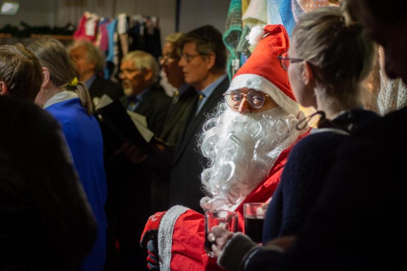 Punanuttuinen Joulupukki väentungoksessa myyjäisvieraiden joukossa.