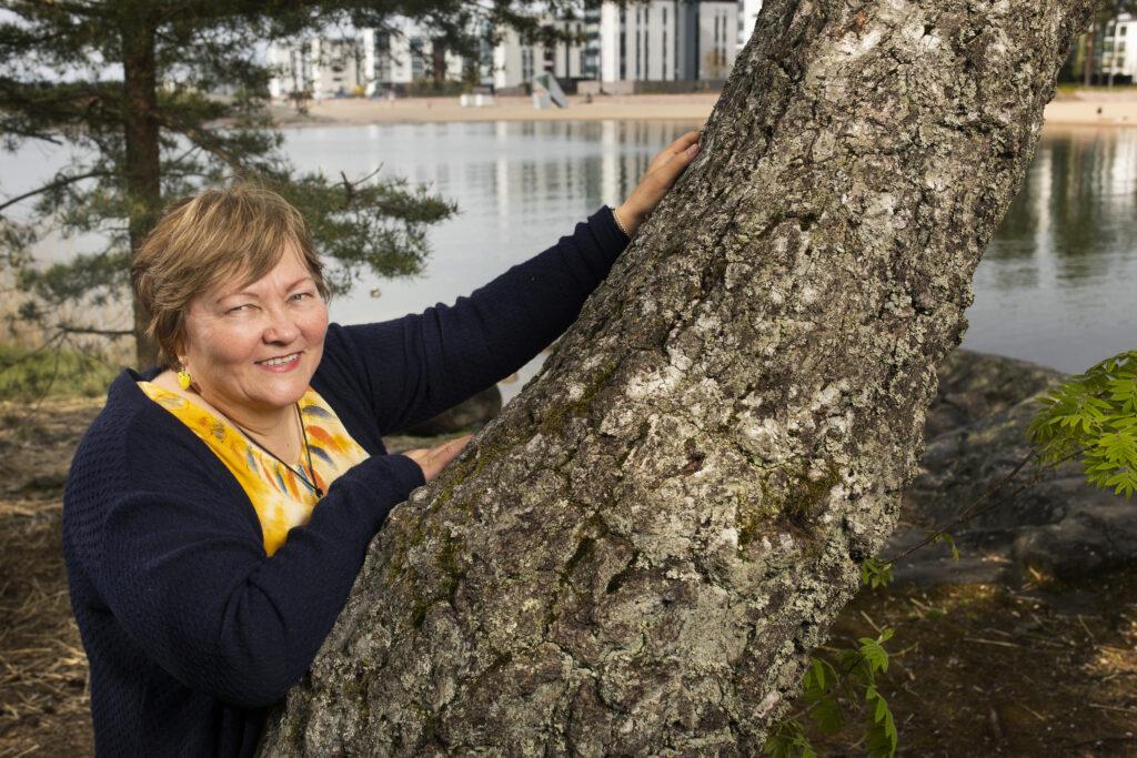 Hymyilevä Pirjo-Sisko Katjaisto nojailee männyn runkoon Hensingissä. Taustalla on Aurinkolahden rantaa ja kerrostaloja.