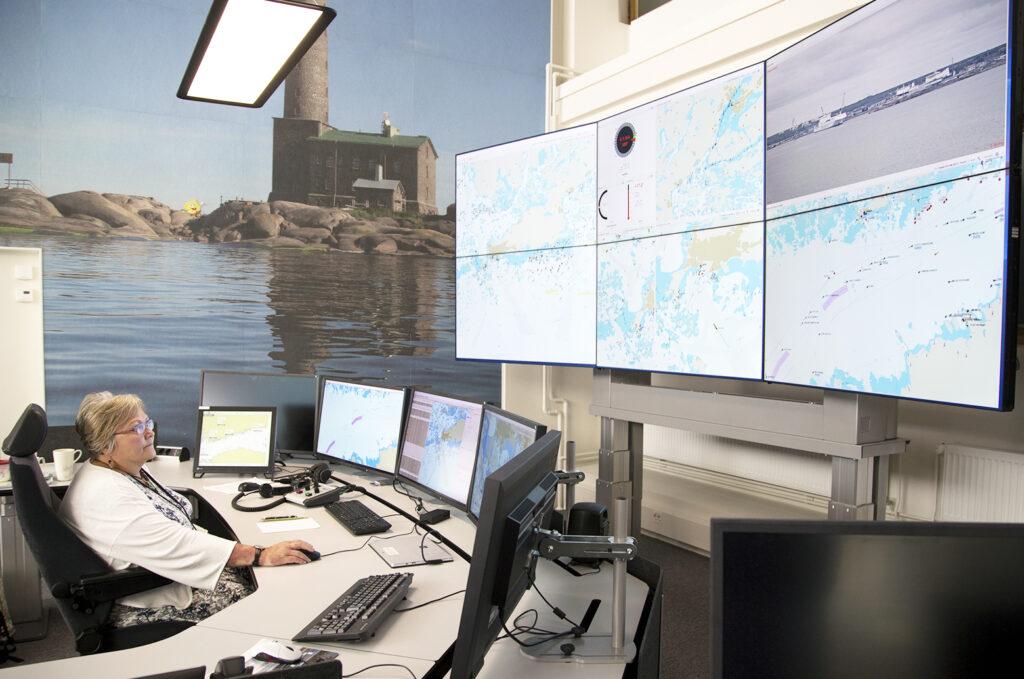 Pirjo-Sisko Katajisto työpaikallaan meriliikennekeskuksessa Helsingissä. Valvottavana on monta tietokone- ja muuta näyttöruutua.