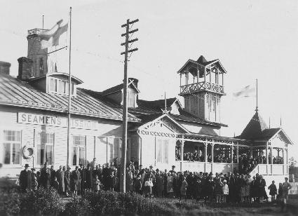 Vaalea puutalo, jossa katettu terassi pitsikoristeluineen ja torni, jonka yläosassa huvimajaa muistuttava tila. Rakennuksen seinässä kyltti Seamens' mission. Talon edustalla suuri joukko ihmisiä.