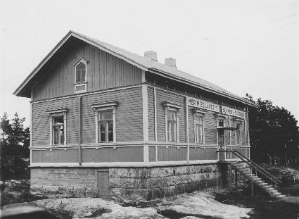 Korkealla kivijalall seisova harjakattoinen puurakennus, jonka pitkällä sivulla on kolme ikkunaa ja ovi portaineen sekä päädyssä kaksi ikkunaa, ullakkoikkuna ja kivijalassa oleva kellarin ovi.