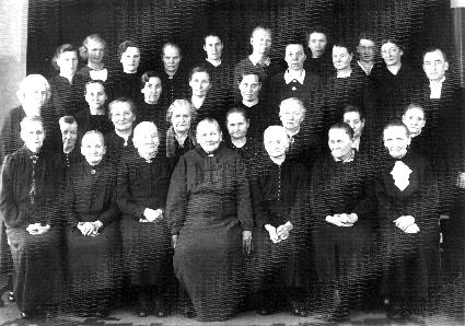 Kolmekymmentä tummiin pukeutunutta vakavailmeistä naista ja miespastori mustavalkoisessa ryhmäkuvassa vuodelta 1942.