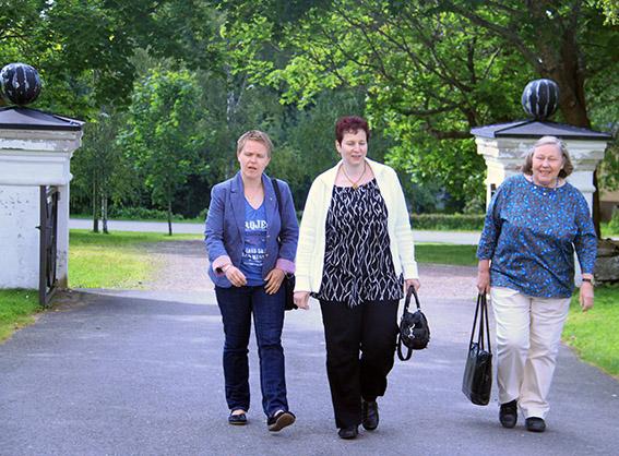 """""""Kolme naista kävelemässä kirkon kiviportista sisään. Taustalla vihreitä lehtipuita."""""""
