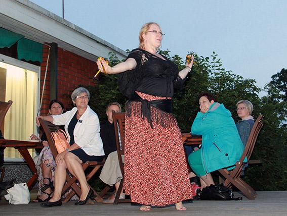 """""""Etualla pihaterassilla tanssiva nainen. Taustalla pöytäryhmän äärellä esitystä katsovia istumassa."""""""
