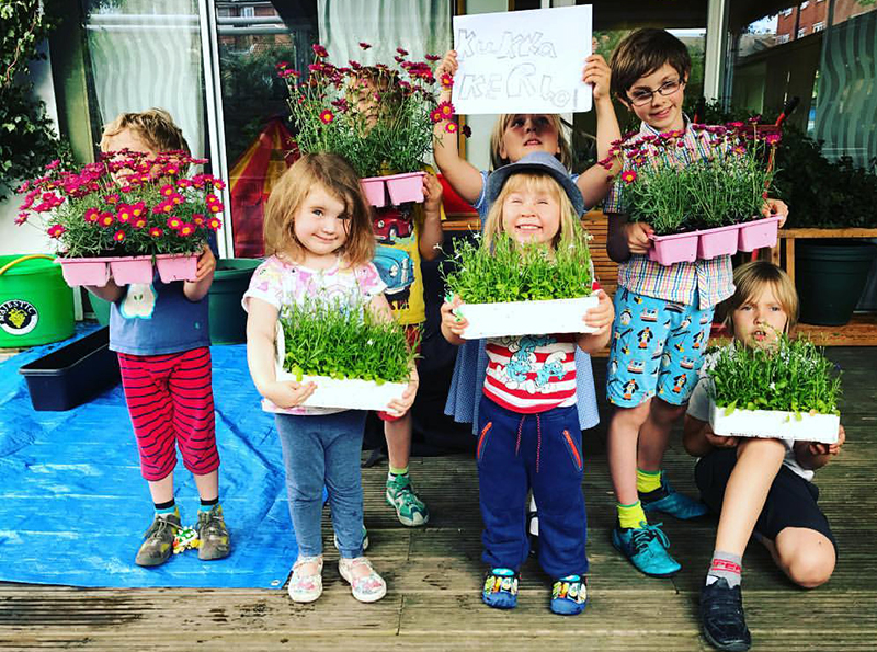 """""""Ryhmä iloisia ja värikkäästi pukeutuneita lapsia pitää käsissään kukkien täyttämiä laatikoita. Yksi lapsista on nostanut ylös kyltin, jossa lukee: Kukkakerho."""""""