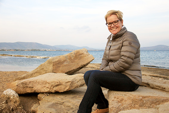 """Hymyilevä Mari Hilonen istuu meren rannan kivenlohkareilla."""