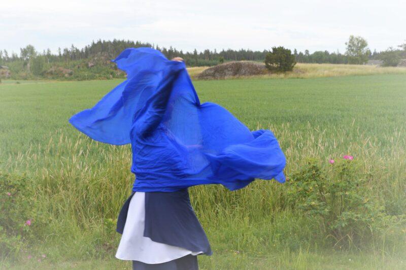 """""""Sinivalkoisiin pukeutunut, pitkätukkainen nainen tanssii ruohikolla pitäen käsissään sinistä kangasta, joka liehuu tuulessa."""""""