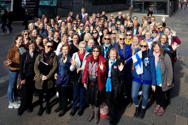 """""""Noin 70 hymyilevää ja vilkuttavaa ihmistä ryhmäkuvassa. Yhdellä henkilöllä on myös Suomen lippu."""""""