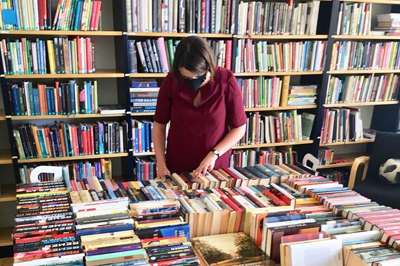 """""""Kasvomaski yllä oleva punapaitainen nainen tutkii pöydällä olevia kirjoja. takanaan seinällä olevassa kirjahyllyssä on runsaasti kirjoja."""""""