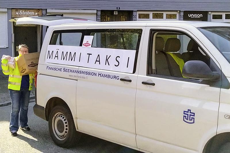 """""""Nainen lastaa Hampurin merimieskirkon valkoiseen pakettiautoon, jossa lukee isoin kirjaimin """"Mämmitaksi"""", laatikoittain Kymppimämmiä."""""""