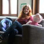 Hymyilevä nuori punatukkainen nainen istuu harmaalla kangassohvalla, jossa myös isot pehmolelut Nasu ja Ihaa.