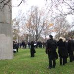 Tummiin pukeutuneita ihmisiä merenkulkijoiden muistomerkin edustalla syksyisenä päivänä.