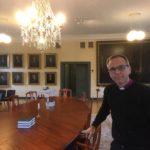 Biskopen i sitt kansli vid stort bordet. På väggen finns många tavlor.