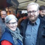 Rennosti pukeutuneet ja nauravaiset Satu ja Valtteri muiden joukossa joulumyyjäisten ruokakatoksen alla Hampurin merimieskirkon pihalla.