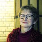 Lähikuva hymyilevästä Eeva Blumenthalista, joka nojaa seurakuntakodilla seinään.