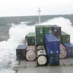 Konteilla lastattu laiva kyntää merta ja tyrskyt lyövät valkoisenaan.