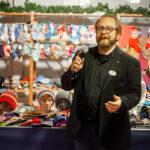 Valtteri Salmi puhuu mikrofoniin. Taustalla on iso määrä värikkäitä villasukkia ja -myssyjä.