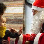 Punanuttuinen joulupukki on antanut karamellin totisena katselevalle lapselle, joka on isänsä sylissä.