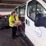 Pirjo Salo vie Kymppimämmilaatikoita Merimieskirkon autoon, jolla tavara toimitetaan asiakkaille.