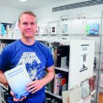 """""""Siniseen Star wars -paitaan pukeutunut hymyilevä mies pitää käsissään kirjaa Suomalaiset maailmalla. Taustalla valkoisissa hyllyissä kirjoja ja lehtiä."""""""